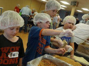 Youth packing meals for children in need